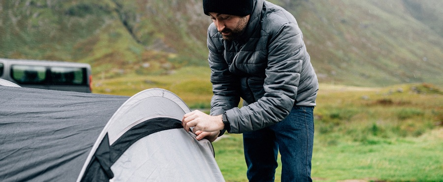 Man opening a tent in the rain