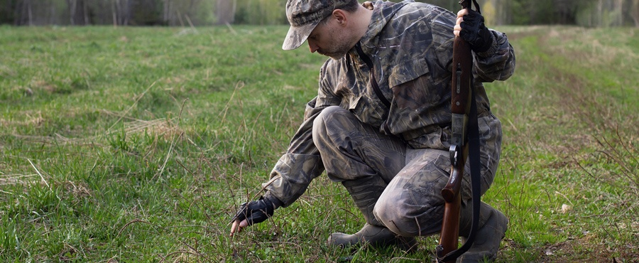 Hunter looking at animal tracks